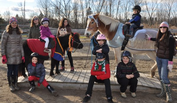 Palomino horse as Elsa from Frozen with black mini horse as Anna standing on a bridge with a group of kids and their moms.